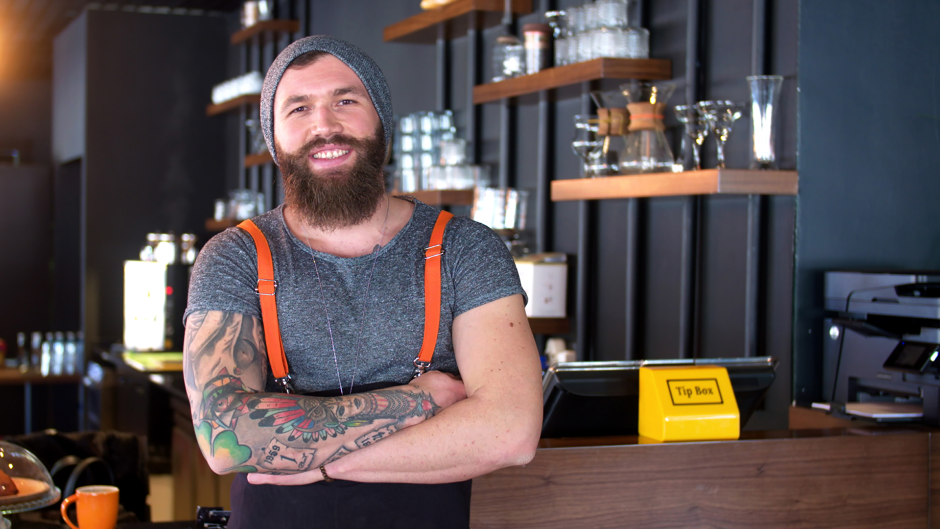 Bearded and tattooed hipster coffee shop owner posing
